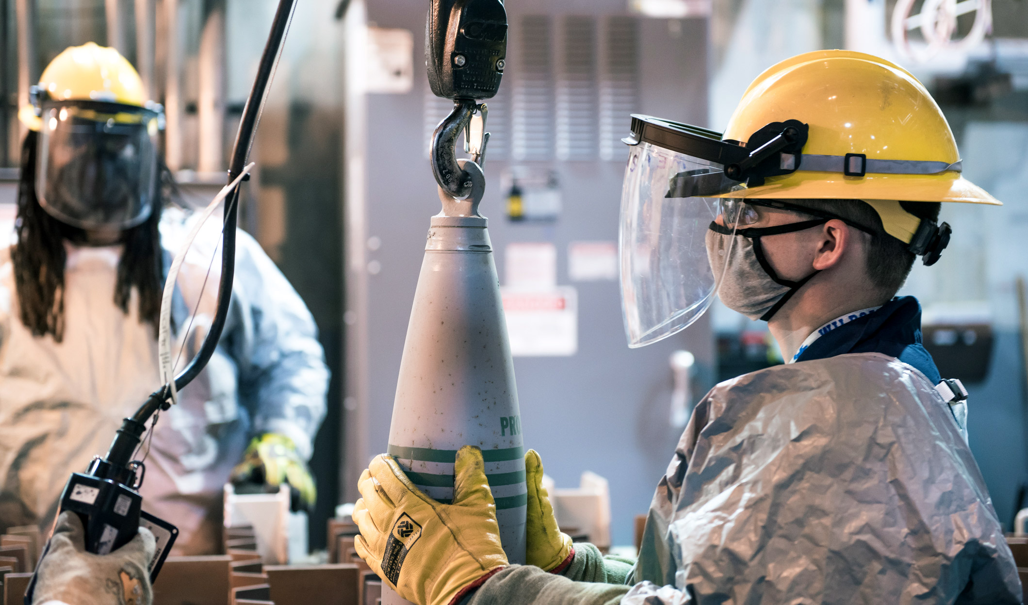 An operator uses a lift assist to safely place a 155mm projectile containing VX nerve agent in a tray to begin the destruction process at the Blue Grass Chemical Agent-Destruction Pilot Plant.